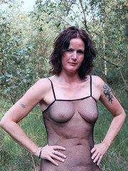 Brunette granny in body stockings masturbating outdoors