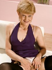 Blonde granny strips off her dress to examine her pink pussy slit and rub her aged gristles