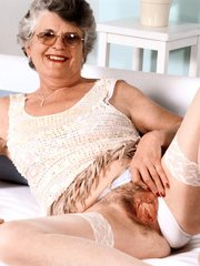 Gray haired mature model spreading her hair covered slit and cramming it with a dildo